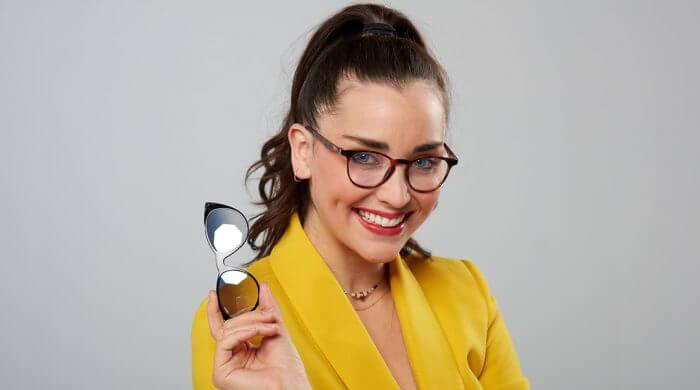 femme tenant une paire de lunettes à la main