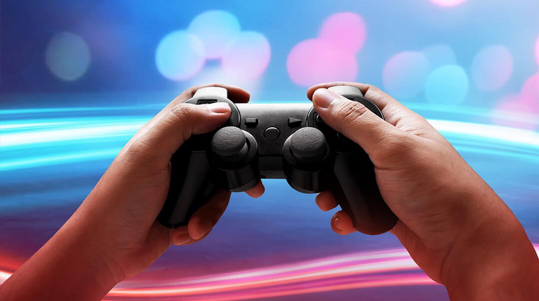 Mains tenant une manette de jeu vidéo sur fond de lumière bleue