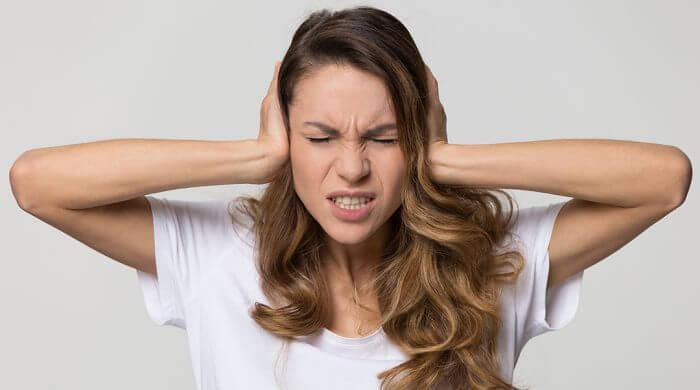 perte d'audition femme se tenant les oreilles à cause du bruit