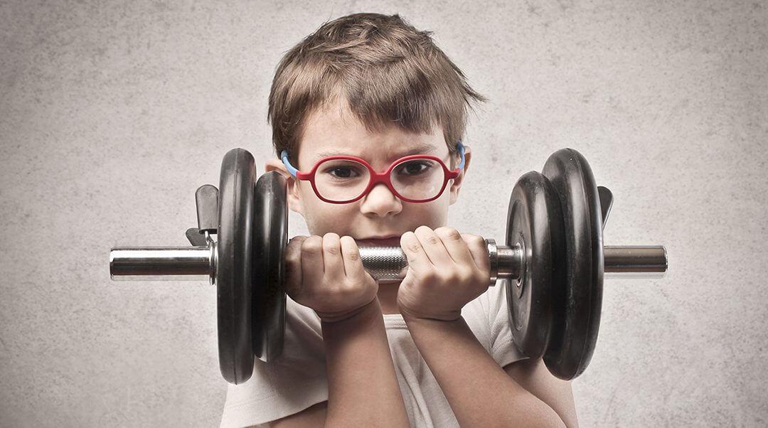 enfant portant des lunettes et tenant des altères