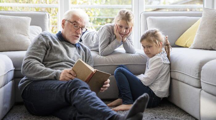 grand-père lisant une histoire à ses petites filles
