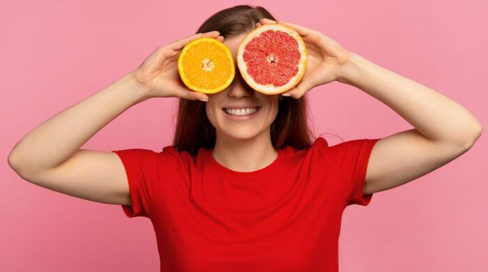 alimentation et santé visuelle: jeune femme tenant une orange et un pamplemousse sur les yeux