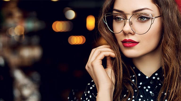 regard d'une jeune femme élégante sur fond de lumières de noël portant des lunettes de vue
