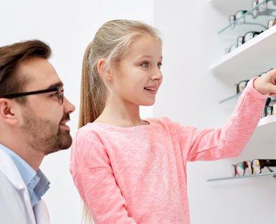 opticien aidant une petite fille à choisir ses lunettes